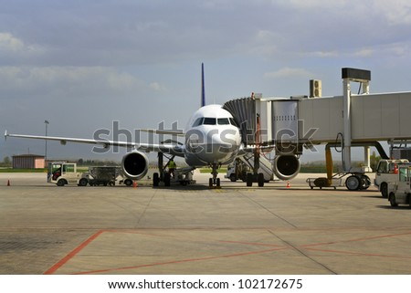 Plane on airport connected to gate sleeve. - stock photo