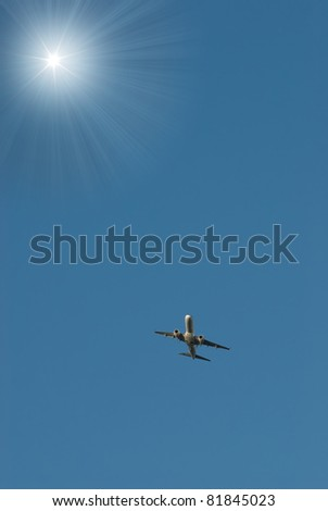 plane on background blue sky flies to sun - stock photo
