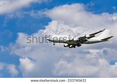 Plane on the blue sky background before landing - stock photo
