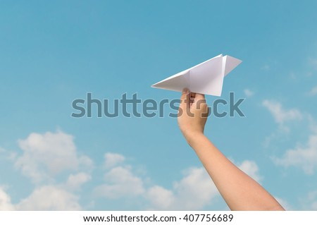 plane paper in children hand and blue sky in cloudy day - stock photo