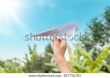 plane paper in children hand in farm and blue sky, in cloudy day - stock photo