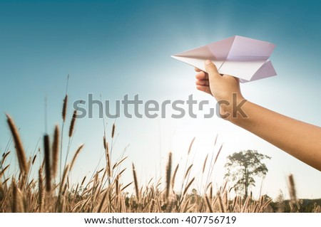 plane paper in children hand, middle in grassland and clear blue sky - stock photo