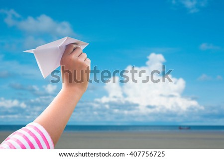 plane paper in children hand over sea and blue sky in cloudy day - stock photo