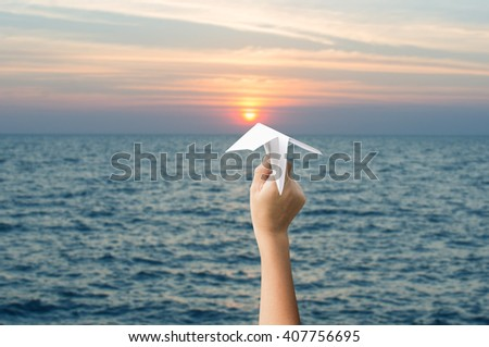 plane paper in children hands and sunset, forward to the target concept. - stock photo