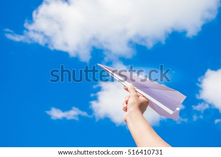 plane paper on human hand with blue sky and cloud background