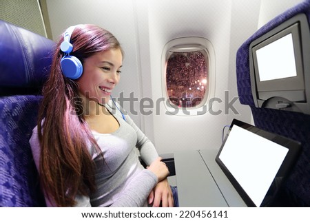 Plane passenger in airplane using tablet computer. Woman in plane cabin using smart device listening to music on headphones. - stock photo