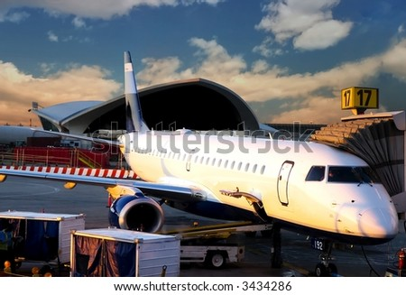 Plane ready for departure, early morning flight.  Beautiful cloudy sky, warm sunrise light. - stock photo