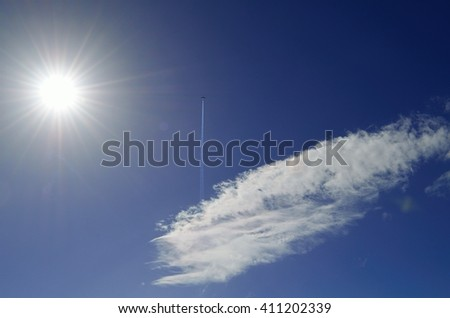 Plane silhouette with sun and cloud