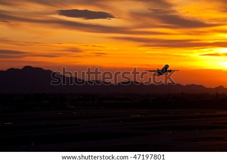 Plane taking off into red sunset. - stock photo