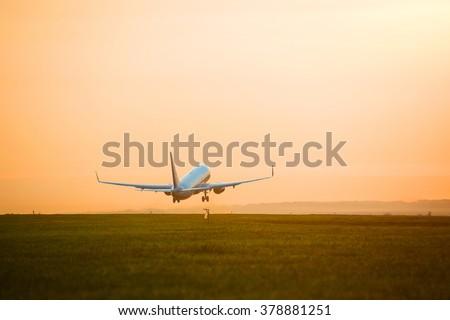 plane taking off sunset - stock photo