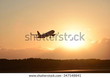 Plane taking off - sunset background - stock photo