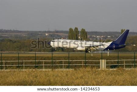 Plane touching ground on the runway - stock photo