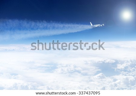 Plane with jet trail over the clouds - Elements of this image furnished by NASA - stock photo