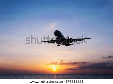 Plane with sky sunset and sea in twilight,  Plane with sea sunset, Plane in colorful sky or transport plane, Plane come down on the land