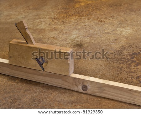 planer on wood in rusty background. old fashioned manual tool