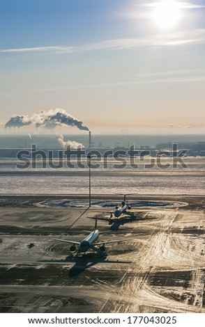 Planes are on the tarmac on a cold winter day in the bright sunlight - stock photo