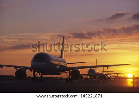 Planes Sitting on Tarmac at Sunset - stock photo