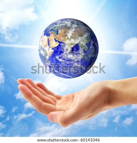 Planet Earth and human hand. Conceptual design. - stock photo