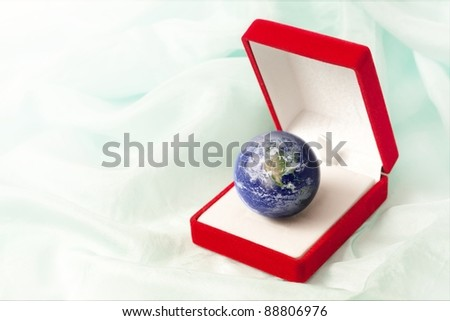 Planet Earth in a jewel box as a precious gift to protect. Image with copy space on the left. Earth globe image provided by NASA. - stock photo