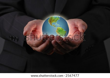 Planet earth in businessman's hands with dark background - stock photo