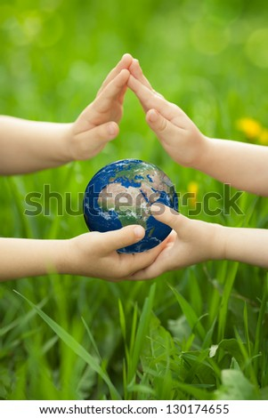 Planet Earth in children`s hands against green spring background. Ecology concept. Elements of this image furnished by NASA - stock photo