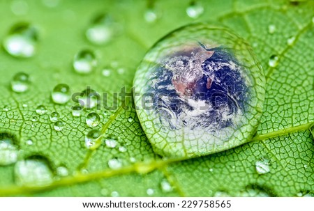 planet earth inside a raindrop closeup on a green leaf (Elements of this image furnished by NASA ) soft focus - stock photo