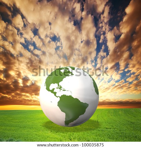 Planet Earth model on green field at sunset. Environement, ecology, clean energy concepts - stock photo