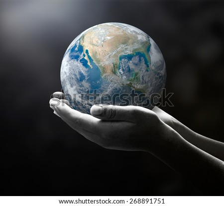 Planet in black and white human hands on nature background. environment concept. Elements of this image furnished by NASA. - stock photo