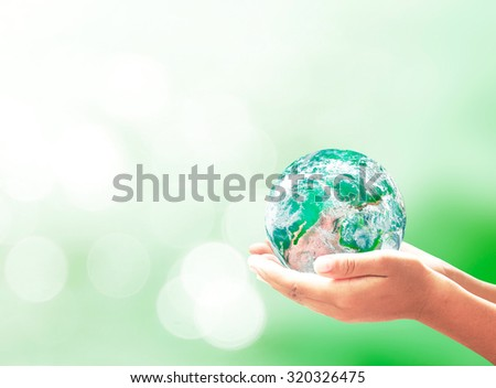 Planet in human hands on beautiful green bokeh nature background. Environment concept. Elements of this image furnished by NASA. - stock photo