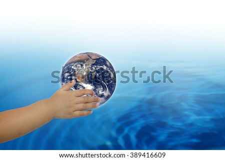Planet in human hands on blurred beautiful nature background. Investment, Ecology, World Environment Day, Elements of this image furnished by NASA. - stock photo