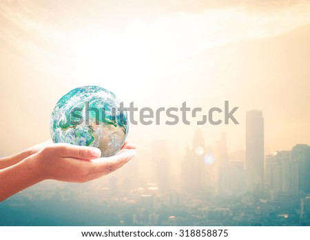 Planet in human hands on blurred warm sunrise over city background with circle light. Ecology concept. World Environment Day concept. Investment concept. Elements of this image furnished by NASA. - stock photo