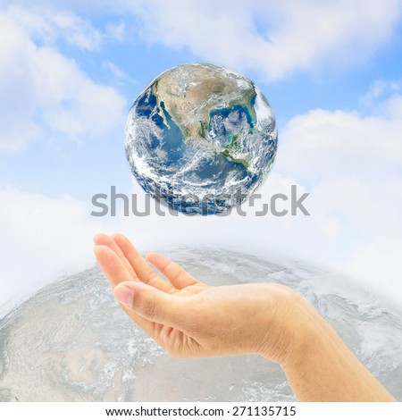 Planet over human hand on natural sky and globe background : Saving environment concept :  Save the earth campaign : Pray for environmental help and support : Elements of this image furnished by NASA  - stock photo