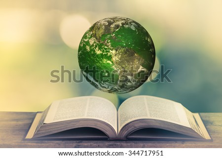 Planet over the open book on a wooden table in nature, green blurry background. World Environment Day. World Mental Health Day concept. Elements of this image furnished by NASA. - stock photo