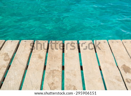 planks of the pier on the background of emerald sea - stock photo