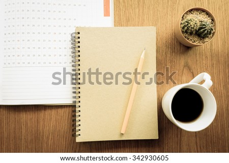 planner and note book on wooden table with vintage style - stock photo