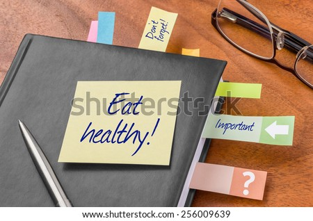 Planner with sticky note - Eat healthy - stock photo