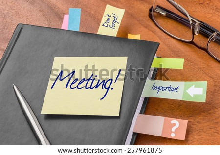 Planner with sticky note - Meeting - stock photo