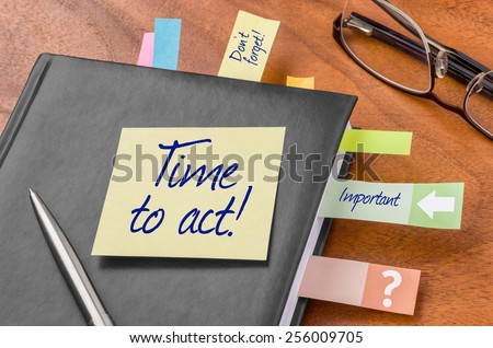Planner with sticky note - Time to act - stock photo