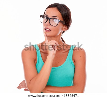 Planning brunette woman with green tank top looking at the camera using a reflective gesture with a finger on her face while contemplating and wearing her long hair back on a white background - stock photo