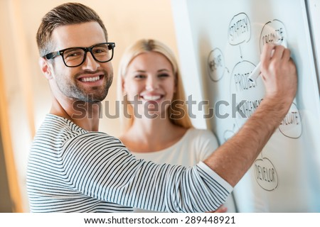 Planning business together. Confident young man and woman looking at camera and smiling while both standing near whiteboard in office - stock photo