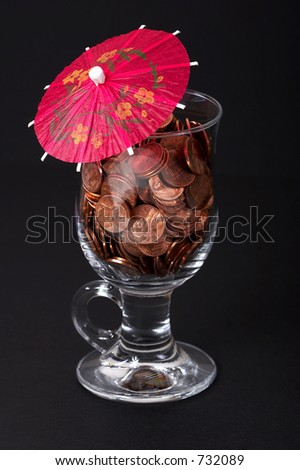 Planning for the retirement - wine glass full of pennies with a party umbrella. - stock photo