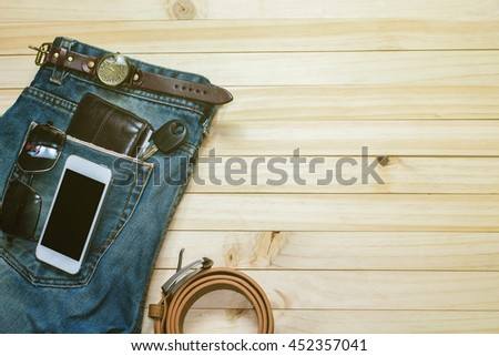 Planning for trip set of travel accessory on wooden background top view,in vintage color tone style,mobile-phone,watch,jean,key,wallet , belts, sunglasses . / copy space