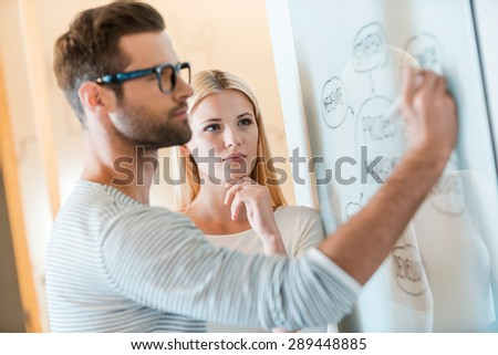 Planning is a key to success. Confident young man sketching on whiteboard while woman standing close to him and holding hand on chin  - stock photo
