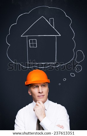 Planning new project. Thoughtful senior man in formalwear and hardhat holding hand on chin and looking away with a chalk drawn house upon his head - stock photo