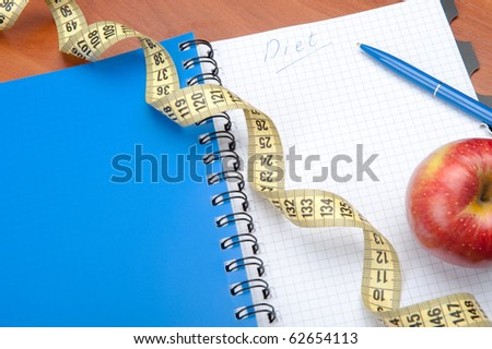 Planning of a diet. A notebook c an inscription - the Diet, a measuring tape, an apple and pen - stock photo