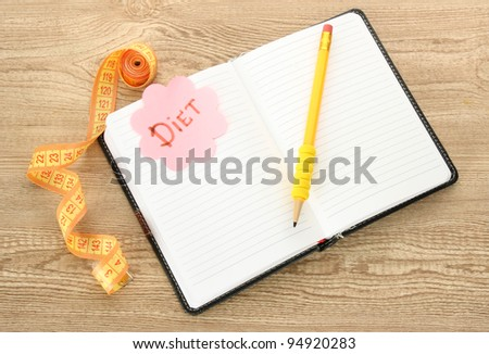 Planning of diet. Notebook measuring tape and pen on wooden table - stock photo