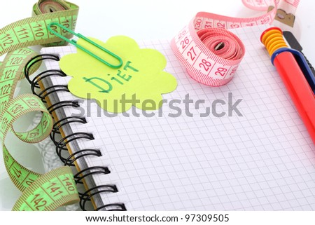 Planning of diet. Notebook measuring tapes and pen isolated on white - stock photo