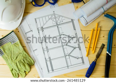 Planning of repair of the house. Repair work. Drawings for building, helmet, mount and others tools on wooden background.