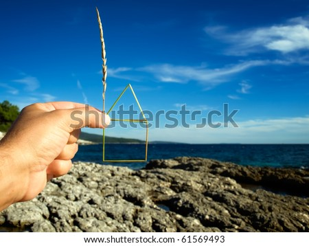 Planning of the construction of a house on the coast , House outline is  made of grass straw. - stock photo