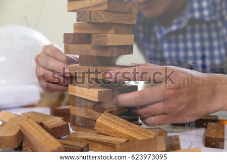 Planning, risk and strategy of project management in architect and engineer man gambling placing wood block on a tower, double exposure with crane and building under construction